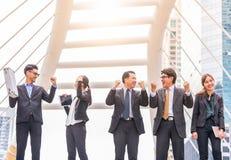Det lyckliga lyckade folket för affärsgruppen räcker lyftt lyckat med gruppen för affären för stadsbakgrund den lyckade med armar arkivfoton