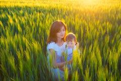 Det lyckliga moderinnehavet behandla som ett barn att le på vetefält i solljus Arkivbild