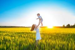 Det lyckliga moderinnehavet behandla som ett barn att le på vetefält i solljus Arkivbilder