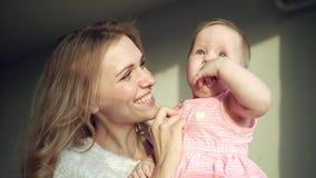 Det lyckliga moderinnehavet behandla som ett barn flickan på händer Gladlynt flicka för mammaomfamninglitet barn lager videofilmer