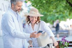 Det lyckliga mogna paret som går runt om staden, kvinna skjuter en cykel arkivbild