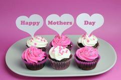 Det lyckliga mors dagmeddelandet över vita hjärtatoppers på rosa färger och vit dekorerade röda sammetmuffin Royaltyfria Bilder