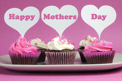 Det lyckliga mors dagmeddelandet på rosa färger och vit dekorerade muffin royaltyfria bilder