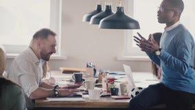 Det lyckliga multietniska affärsfolket samarbetar i vinden som coworking Vänner tycker om att arbeta tillsammans i ljust sunt kon lager videofilmer
