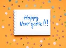 Det lyckliga nya året för inskrift på en vit anteckningsbok Orange bakgrund med konfettier arkivfoton
