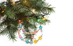 Det lyckliga nya året och den glade julkortet prydde med pärlor bokstavsgirlanden på frunch för granträd Arkivbild