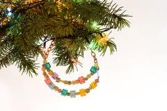 Det lyckliga nya året och den glade julkortet prydde med pärlor bokstavsgirlanden på frunch för granträd Royaltyfri Fotografi
