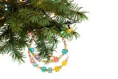 Det lyckliga nya året och den glade julkortet prydde med pärlor bokstavsgirlanden på frunch för granträd Royaltyfri Bild