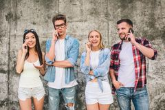 Det lyckliga och upptagna folket står på grå bakgrund och talar på telefonen De är lyckliga och emotionella Endast en Royaltyfri Bild
