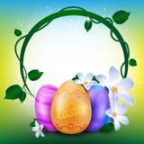 Det lyckliga påskhälsningkortet med den runda ramen av den målade ägg och våren blommar Arkivfoton