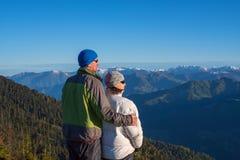 Det lyckliga paret av handelsresande beundrar gryningen i bergen Royaltyfri Foto