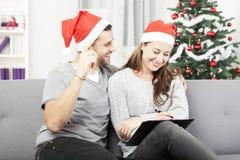 Det lyckliga paret gör en önskelista för jul Royaltyfria Foton