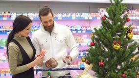 Det lyckliga paret köper livsmedel för jul på livsmedelsbutiken stock video