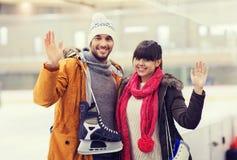Det lyckliga paret med åker skridsko på att åka skridskor isbanan arkivbild