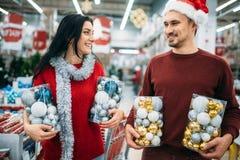 Det lyckliga paret rymmer askar med julleksaker fotografering för bildbyråer