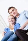 Det lyckliga paret sitter på den vita lädersofaen arkivfoton