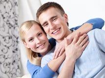 Det lyckliga paret sitter på soffan arkivbild