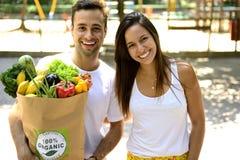 Det lyckliga paret som bär en pappers- påse för återanvändning av organisk grönsakans, bär frukt mycket. Arkivfoton
