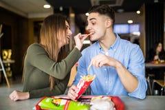 Det lyckliga paret som matar sig som äter, steker under lunchtime i snabbmatkafé tomat för smörgås för grönsallat för skräp för f fotografering för bildbyråer