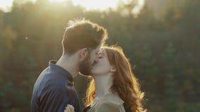 Det lyckliga paret står i omfamning och kysser sig på solnedgång arkivfilmer