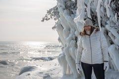 det lyckliga personanseendet bredvid is täckte träd på grottapunkt parkerar längs Lake Michigan i vinter royaltyfri foto