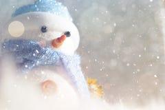 Det lyckliga snögubbeanseendet i vinterjul snöar bakgrund Glad jul och hälsningkort för lyckligt nytt år med kopia-utrymme Arkivfoto