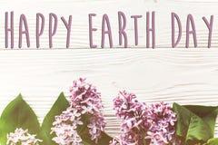 Det lyckliga tecknet för text för jorddagen på härlig lila blommar på lantligt Arkivfoton