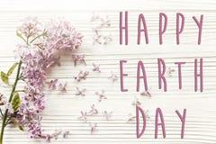 Det lyckliga tecknet för text för jorddagen på härlig lila blommar på lantligt Arkivbilder