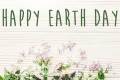 Det lyckliga tecknet för text för jorddagen på härlig lila och tusensköna blommar nolla Arkivfoto