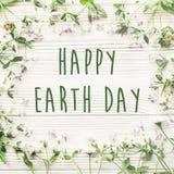 Det lyckliga tecknet för text för jorddagen på härlig lila och tusensköna blommar nolla Arkivbilder