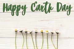 Det lyckliga tecknet för text för jorddagen på härlig tusensköna blommar på lantlig w Royaltyfri Fotografi