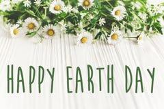 Det lyckliga tecknet för text för jorddagen på härlig tusensköna blommar på lantlig w Arkivfoton