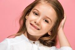 Det lyckliga tonåriga flickaanseendet och le mot rosa bakgrund Royaltyfri Fotografi
