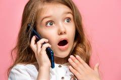 Det lyckliga tonåriga flickaanseendet och le mot rosa bakgrund Royaltyfria Foton