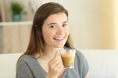 Det lyckliga tonåriga innehavet ett kaffe med mjölkar att se dig arkivfoto