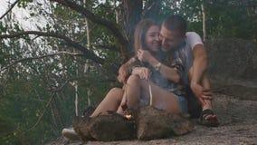 Det lyckliga tonåringparet som friying korvar på rökig brasa i den unga mannen för skogen kysser lyckligt, hans flickvän stock video
