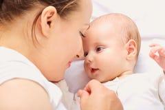 Det lyckliga ung flickainnehav hänger lös på en vitbakgrund babyansiktemoder till Fotografering för Bildbyråer