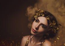 Det lyckliga ung flickainnehav hänger lös på en vitbakgrund Flicka med idérikt smink och med guld- ögonfrans Den grekiska gudinna royaltyfria foton