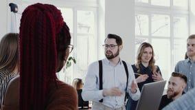 Det lyckliga unga affärsfolket arbetar på den bekväma sunda kontorsarbetsplatsen, framstickandemannen som leder RÖD EPOS för möte stock video
