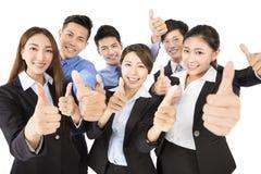 Det lyckliga unga affärslaget med tummar gör en gest upp fotografering för bildbyråer