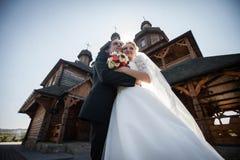 Det lyckliga unga caucasian paret poserar framme av historiskt trä royaltyfri bild