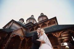 Det lyckliga unga caucasian paret poserar framme av historiskt trä arkivfoton