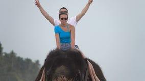 Det lyckliga unga paret rider på en elefant på bakgrunden av ett tropiskt hav lager videofilmer