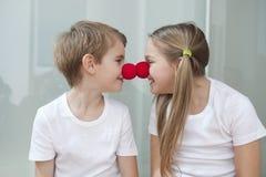 Det lyckliga unga syskonet i vita tshirts som gnider clownen, noses mot varandra Royaltyfri Foto