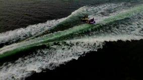Det lyckliga upphetsade folket som rider det uppblåsbara vattenröret, glider dragningen med det motoriska fartyget, i att förbluf stock video