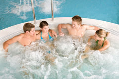 det lyckliga varma folket kopplar av överkanten badar sikt Arkivfoton