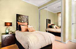 Det lyxiga inre sovrummet på natten med en modern enkel säng inkluderar Fotografering för Bildbyråer