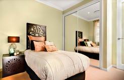 Det lyxiga inre sovrummet på natten med en modern enkel säng inkluderar Royaltyfri Bild