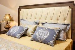 Det lyxiga moderna stilsovrummet i guling och blått tonar, inre av ett hotellsovrum, kuddar med en modellprydnad Arkivfoton