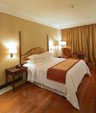 Det lyxiga rymliga sovrummet med trädurken och färgad guld hänger upp gardiner Arkivbilder
